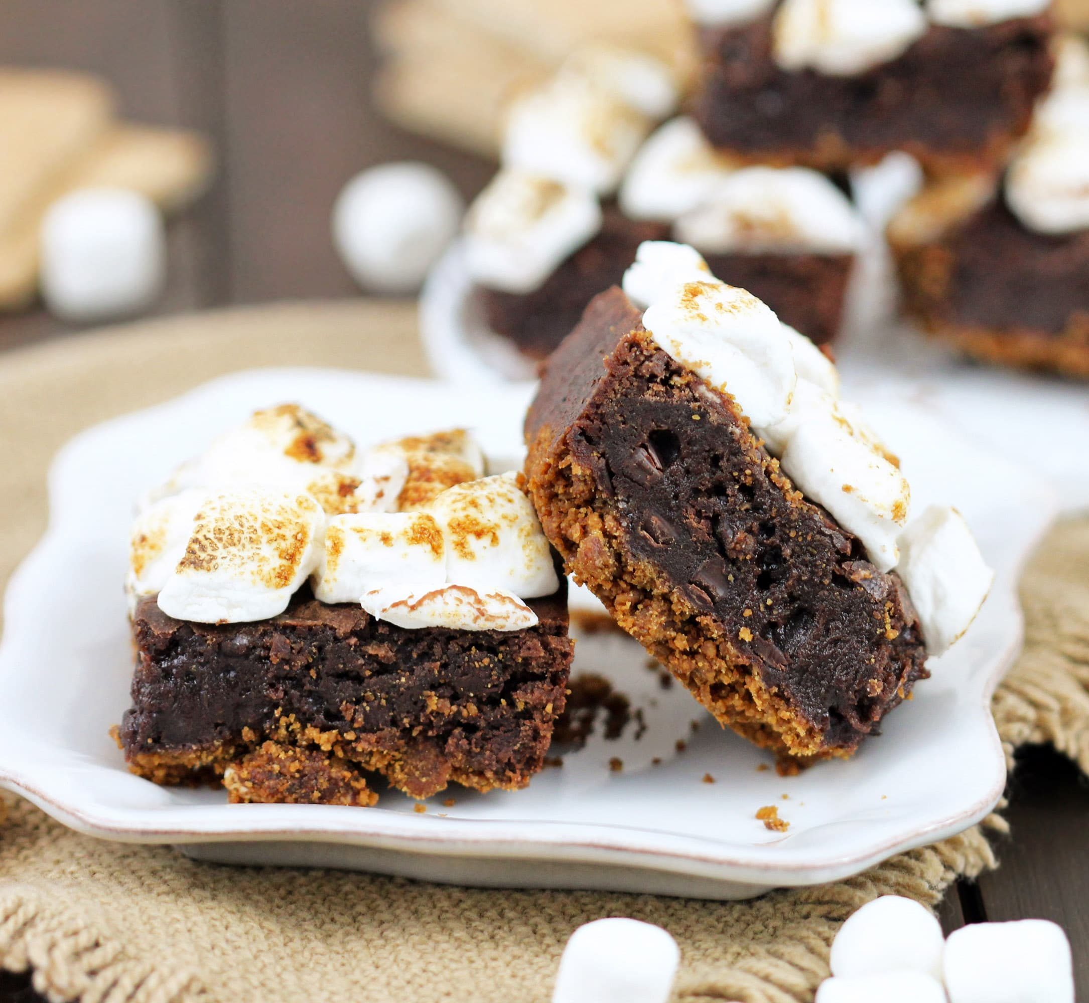 S'mores Brownies with just 6 ingredients! Satisfy your s'mores craving with these delicious brownies. Made with an actual graham cracker crust, fudge brownie filling, and a sweet marshmallow studded topping, every bite is full of salty-sweet graham cracker flavor, decadent chocolate, and toasted mallows. Healthy Dessert Recipes at the Desserts With Benefits Blog (www.DessertsWithBenefits.com)