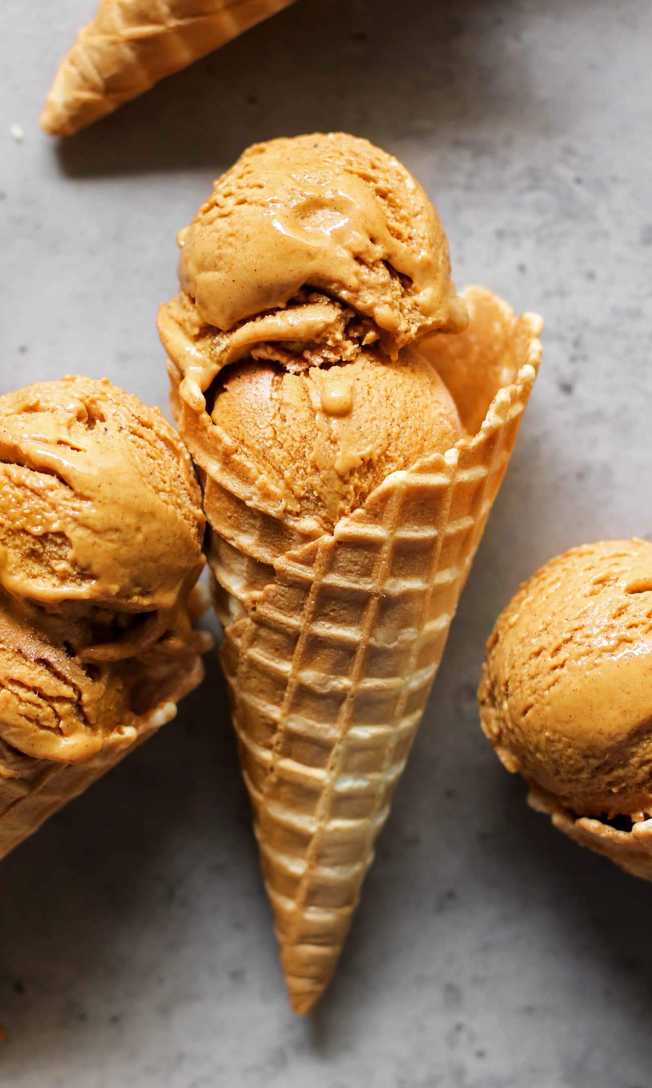 This Healthy Pumpkin Ice Cream is ULTRA creamy, perfectly spiced, and sweet enough to satisfy your sweet tooth. Best of all, it's made with 100% good-for-you ingredients! No heavy cream, no eggs, and no refined sugar! Instead, this version is low fat, refined sugar free, high protein, and gluten free too! #pumpkin #pumpkinpiespice #allnatural #refinedsugarfree #healthyicecream #highprotein #lowfat #easy #homemadeicecream